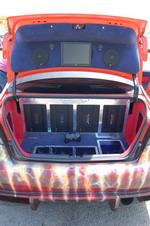 Багажник Civic поделен на сферы влияния между батареей усилителей Steg, монитором для PlayStation, мощным гелевым аккумулятором и баллоном закиси азота ZEX. При этом качество исполнения и подгонки всех элементов впечатляет. Кроме того, и сейчас багажник может | Honda Civic Ferio RS / Nissan Skyline